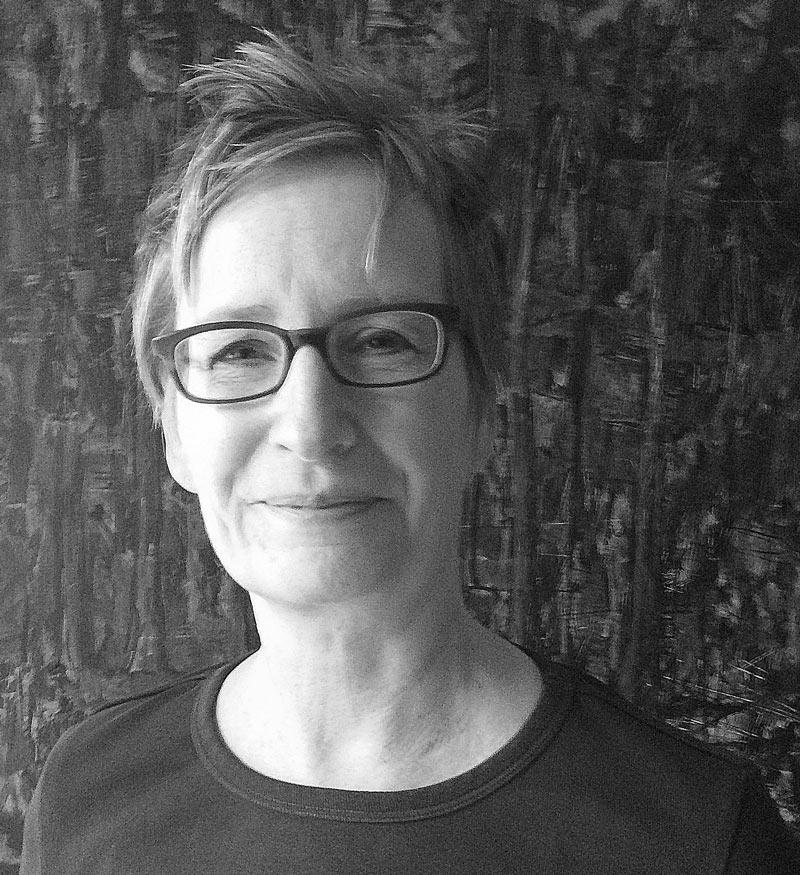 Schwarzweiß Portraitfoto von Eeva Rantamo. Eine Frau mit Brille und kurzen, blonden Haaren lächelt freundlich in die Kamera. Sie trägt ein einfaches, dunkles Shirt mit rundem Ausschnitt.